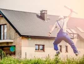 man jumping for joy with building plans