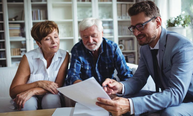 Senior couple planning their investments with financial adviser in living room