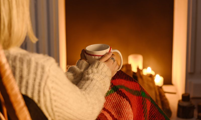 Partial view of woman in checkered blanket holding mug of cocoa at home